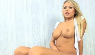 A blonde is masturbating in front of the camera in an alluring fashion